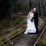 Bride and groom kissing on the railroad tracks in parksville bc