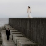 bride and groom walking the breakwater in victoria