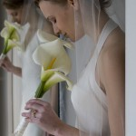 bride reflected in in mirror holding orchids.