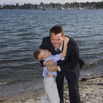 groom and nephew hugging by the water
