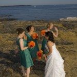 Laughing wedding party by the ocean