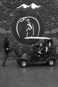 photo of a man driving a golf cart and his woman stopping him